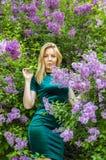 Flicka p? bakgrunden av ett blommande lila tr?d fotografering för bildbyråer
