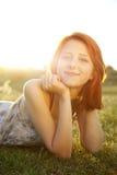 Flicka på det gröna gräsfältet på solnedgången. Arkivfoton