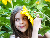 Flicka på fältet av solrosor Arkivfoto