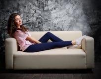 Flicka på soffan på mörkt rum Arkivbild