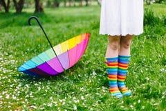 Flicka` s lägger benen på ryggen i färgrika regnkängor med regnbåge-paraplyet på bakgrunden Vår utomhus Arkivfoton