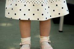 Flicka` s lägger benen på ryggen med skor och klänningen royaltyfria bilder