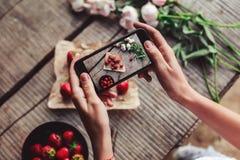 Flicka` s räcker att ta fotoet av frukosten med jordgubbar vid smartphonen Sund frukost, royaltyfri fotografi