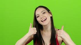 Flicka s som har gyckel och uppvisning tummar upp grön skärm långsam rörelse lager videofilmer