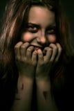 Flicka som är besatt vid en demon med ett illavarslande leende royaltyfria foton