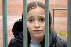 Flicka som är inlåst bak ett staket royaltyfri bild