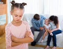 Flicka som är ledsen på grund av svartsjuk mer ung syster till föräldrar arkivbilder