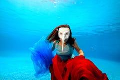 Flicka som är undervattens- i en vit maskering som poserar på den blåa bakgrunden Arkivfoto