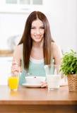 Flicka som äter banta sädesslag och orange fruktsaft arkivbilder