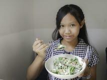 Flicka som äter Caesar sallad Royaltyfri Bild