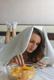 Flicka som äter chiper i säng- och hålla ögonen pånyheterna i telefon royaltyfri bild