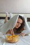 Flicka som äter chiper i säng- och hålla ögonen pånyheterna i telefon Royaltyfria Foton