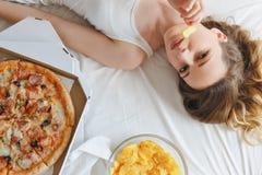 Flicka som äter chiper på sängen som står bredvid pizza Royaltyfri Fotografi