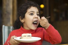 Flicka som äter den söta pajen royaltyfria foton