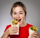 Flicka som äter den stora smörgåsen Arkivbild