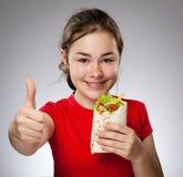 Flicka som äter den stora smörgåsen som visar OK tecknet Royaltyfria Bilder