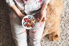 Flicka som äter den sunda frukostbunken med yoghurt och bär royaltyfri fotografi