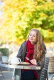 Flicka som äter dillandear i ett parisiskt kafé Arkivfoto