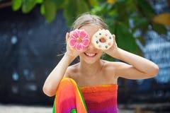 Flicka som äter donuts Fotografering för Bildbyråer