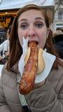 Flicka som äter en bratwurstkorv Arkivfoto