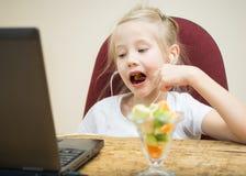 Flicka som äter fruktcoctailen bredvid bärbara datorn Royaltyfri Fotografi