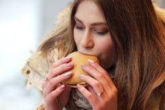 Flicka som äter hamburgaren royaltyfri foto