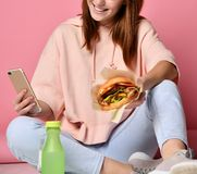 Flicka som äter hamburgaren och ser telefonen E arkivfoto