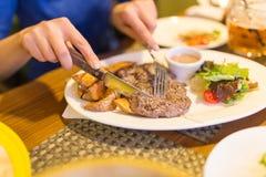 Flicka som äter kött med sallad i en restaurang fotografering för bildbyråer