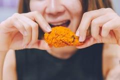 Flicka som äter läcker smaklig stekt kyckling fotografering för bildbyråer