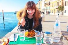 Flicka som äter middag skaldjur i ett utomhus- kafé på den storslagna kanalen i Venedig arkivfoto