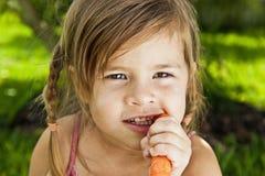 Flicka som äter moroten Arkivbild