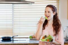 Flicka som äter någon sallad i kök Arkivfoton