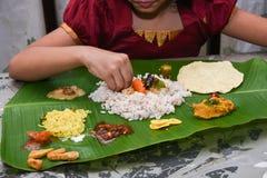 Flicka som äter Onam Sadhya med handformen Kerala Indien arkivbilder