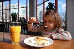 Flicka som äter ostkaka med en dela sig Arkivfoton