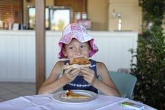 flicka som äter pizza i ett kafé royaltyfria foton