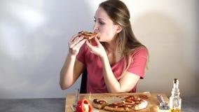 Flicka som äter pizza på tabellen stock video