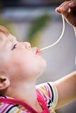 Flicka som äter spagetti fotografering för bildbyråer