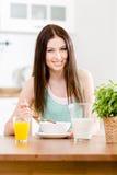 Flicka som äter sund mysli och orange fruktsaft arkivbilder