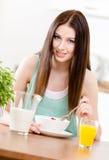 Flicka som äter sunda sädesslag och orange fruktsaft arkivbilder