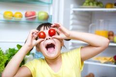 Flicka som äter tomater som står det near kylskåpet Royaltyfri Bild