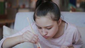 Flicka som äter upp sushi och doppet i sås i sushistång, slut arkivfilmer