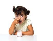 Flicka som äter yoghurt Arkivfoto