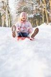 flicka som åka släde snöig skogsmark Royaltyfri Bild