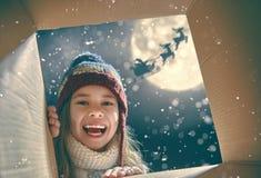 Flicka som öppnar en gåva på jul royaltyfri bild
