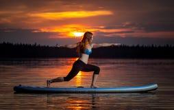 Flicka som övar yoga på paddleboard i solnedgången på den sceniska sjön Velke Darko royaltyfria bilder