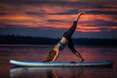 Flicka som övar yoga på paddleboard i solnedgången på den sceniska sjön Velke Darko royaltyfri fotografi