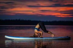 Flicka som övar yoga på paddleboard i solnedgången på den sceniska sjön Velke Darko arkivfoto