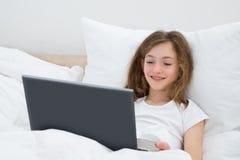 Flicka som använder bärbara datorn i sovrum Arkivfoto
