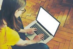 Flicka som använder bärbara datorn och att skriva Arkivbilder