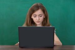 Flicka som använder bärbara datorn på skrivbordet Royaltyfri Fotografi